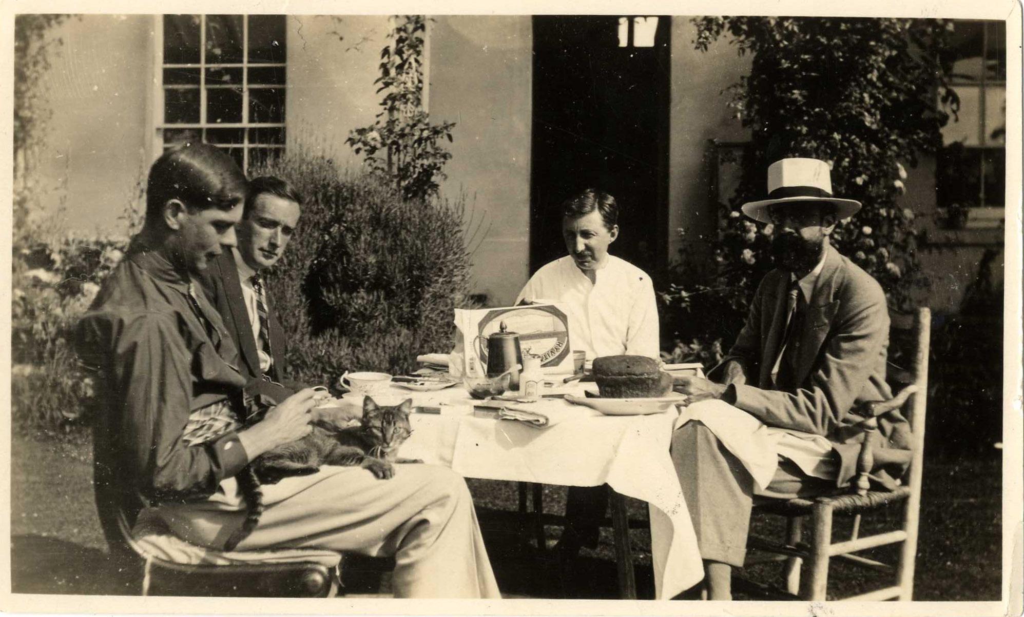 Sebastian Sprott (with the cat), Gerald Heard, EM Forster and Lytton Strachey, at Ham Spray House, 1920s. (EMF/27/351)