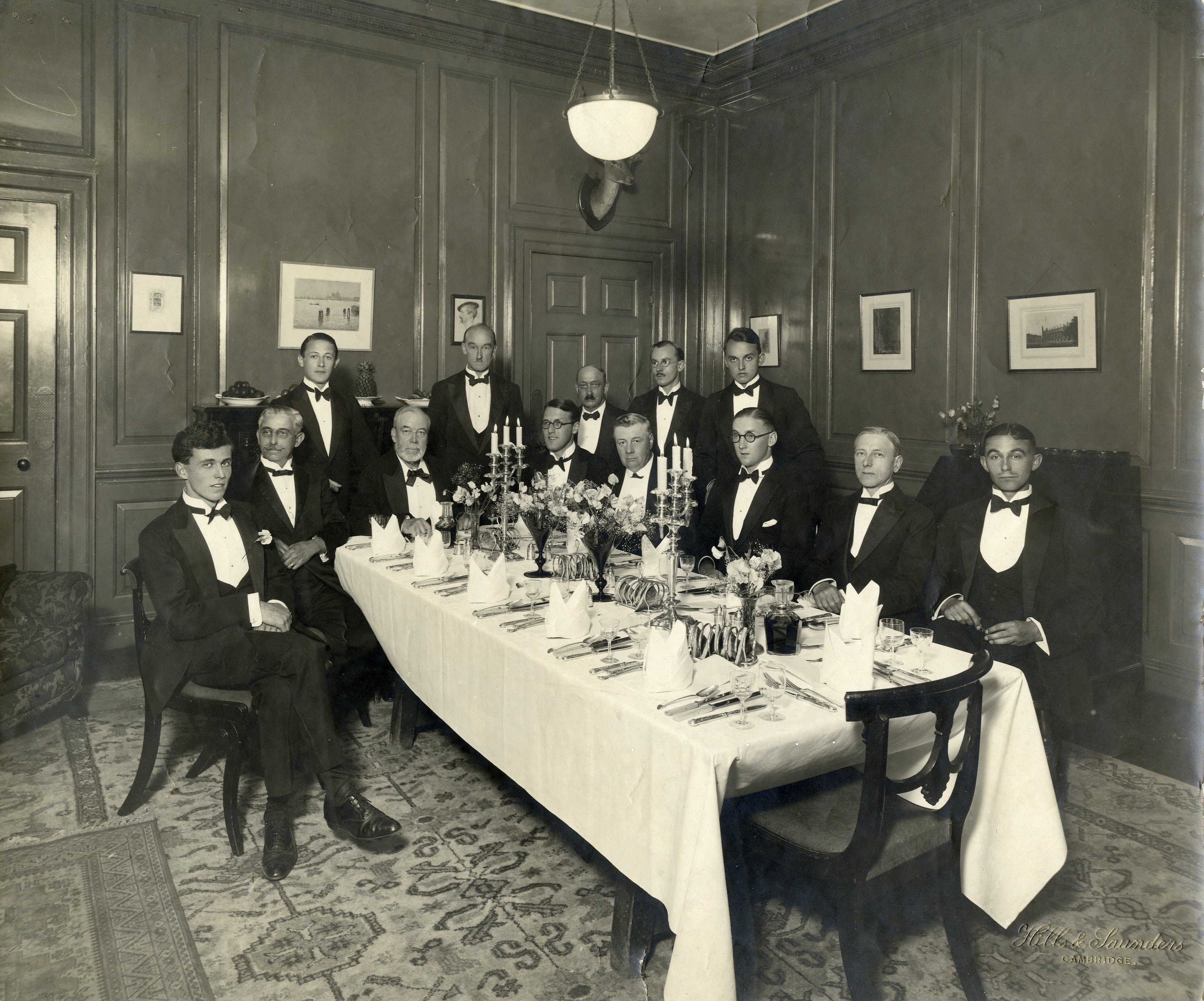 Arthur Henry 'Daddy' Mann at a dinner party given by Rutherford Ikin in G1, with choral scholars, in honour of Mann's 50th anniversary as organist. Photograph taken by Hills and Saunders, 1926. [KCPH/2/13]