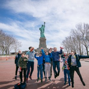 The choristers in front of the Statue of Liberty